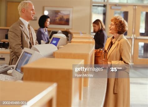 Woman Talking With Bank Teller At Reception Desk Side View